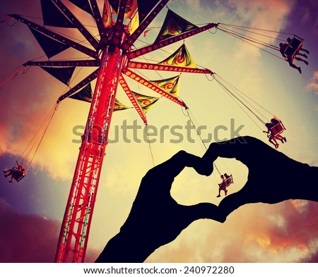 a silhouette of hands in the shape of a heart over a fair background toned with a retro vintage instagram filter effect - stock photo