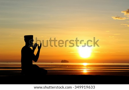 A silhouette of islamic prayjng at sunset.