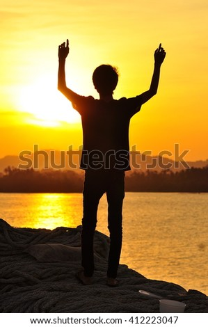 A silhouette of man enjoying the view of sunset with the background of orange sunset. stock photo . copy space