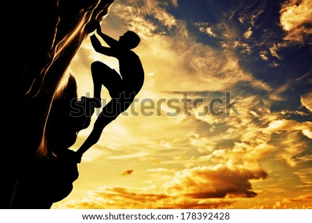 A silhouette of man free climbing on rock, mountain at sunset. Adrenaline, bravery, leader. - stock photo