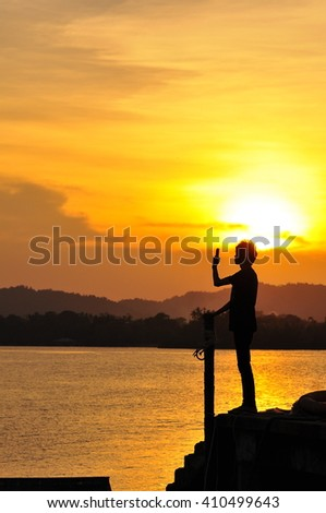 A silhouette of man taking photos of sunset with mobile phone with the background of orange sunset. stock photo . copy space