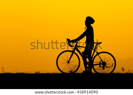 A silhouette of man wearing glasses standing with bicycle and him looking at the sky in sunset.