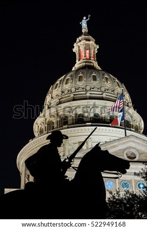 A silhouette of Terry's Texas Rangers Monument framed by the Texas Capitol Dome at night in downtown Austin.