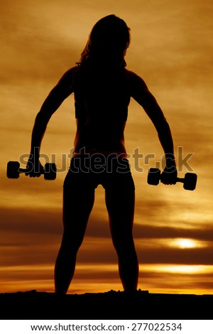 A silhouette of the back of a woman working out with her weights. - stock photo