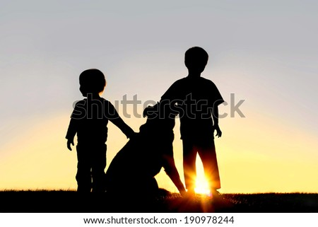 A silhouette of two children; a little boy and his toddler brother standing outside at sunset, petting their German Shepherd dog. - stock photo