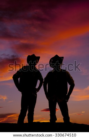 A silhouette of two cowboys standing in the outdoors. - stock photo
