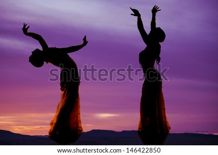 A silhouette of two women belly dancing. - stock photo