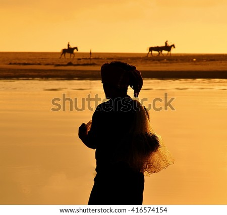 A silhouette of unknown traditional Fishermen hold the fishing nets at a beach in vibrance orange - stock photo