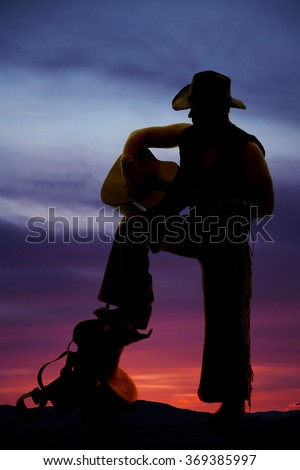 A silhouette on a saddle with his foot up playing his guitar.