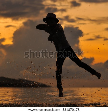 A silhouette on the beach with a background of a wonderful sunset: a gallant little boy in fedora hat is jumping from dads hands and flutters over the water. There is a lot of splashes