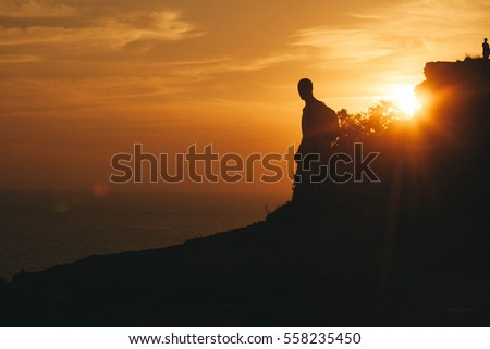 A silhouette stand by the sea on the edge of the cliff. Man enjoying a sunset or sunrise from top of the mountain in summer. Traveler see the sunrise at the peak of mountain.