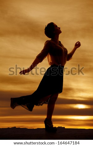 A silhouette woman sheer skirt leg up back - stock photo