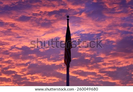 A Silhouetted American Flag Against a Beautiful Dramatic Cloudscape with Bright Pink, Red, and Blue Clouds Basking in the Light of the Rising Sun - stock photo