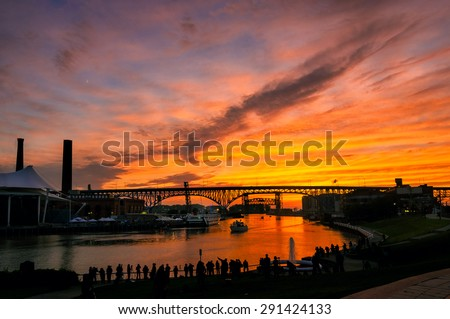 A silhouetted crowd of photographers lines the east bank of the Cuyahoga River in Cleveland to shoot the summer solstice sunset