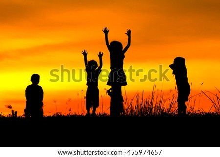 A silhouettes happy children on summer meadow running and jumping