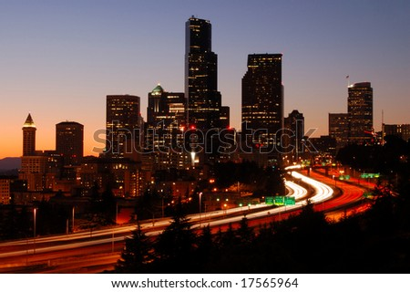 A silhouttle of the Seattle downtown with colorful freeways in foreground