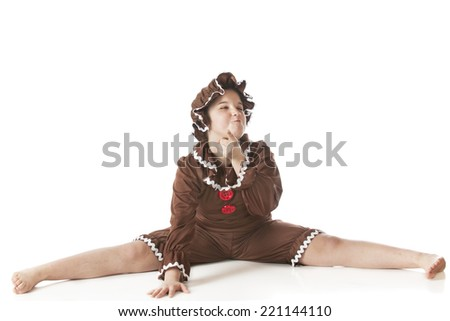 A silly elementary girl doing the splits in her gingerbread outfit.  On a white background. - stock photo