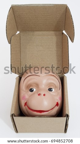 A silly smiling monkey face in an open box.