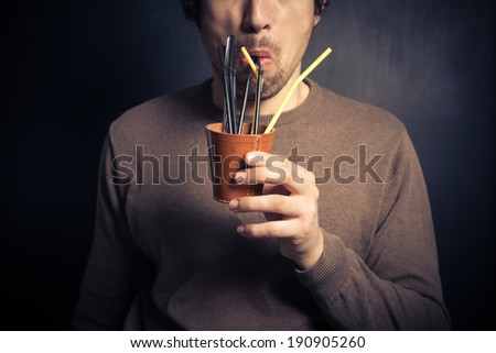 A silly young man is drinking from a leather cup with a bunch of colorful straws - stock photo