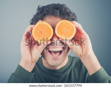 A silly young man is pretending to use two orange halves as binoculars - stock photo