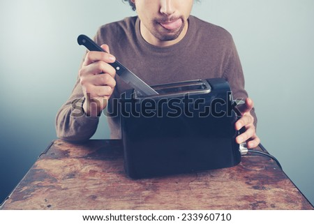 A silly young man is sticking a knife into an electric toaster - stock photo