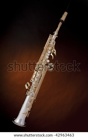 A silver and gold professional soprano saxophone isolated against a spotlight gold background.
