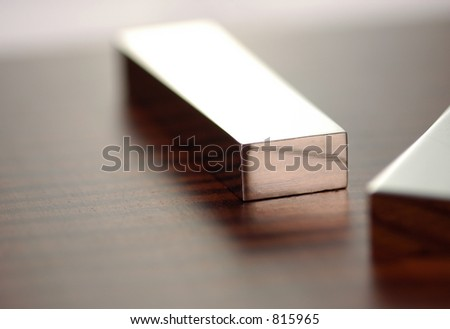 A silver bar sits in the middle of the frame with the corner of another in the front with very shallow depth of field - stock photo