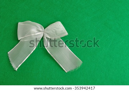 A silver bow isolated against a green background