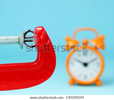 A silver Euro symbol placed in a red clamp with a pastel blue background, with an orange alarm clock in the background indicating the pressure on the pound sterling. - stock photo