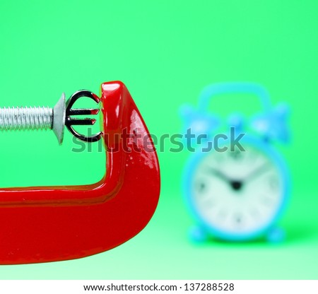 A silver Euro symbol placed in a red clamp with a pastel green background, with a blue alarm clock in the background indicating the pressure on the Euro. - stock photo