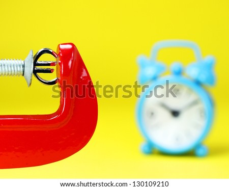 A silver Euro symbol placed in a red clamp with a yellow background, with a blue alarm clock in the background indicating the pressure on the pound sterling. - stock photo