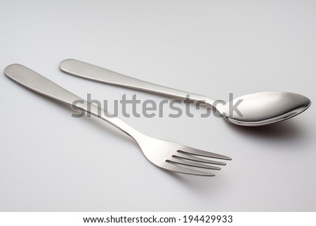 a silver fork with spoon isolated on gray background