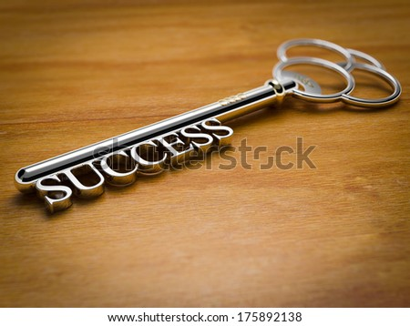 A silver key with the word Success on wooden surface
