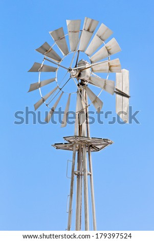 A silver metallic windmill stands tall against a clear blue sky over America's Midwest. - stock photo