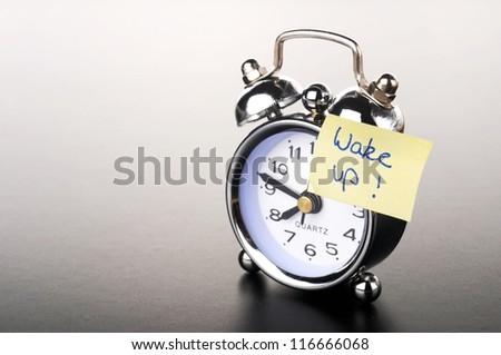 a silver retro alarm bell with paper notice on black background - stock photo