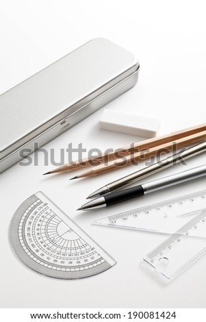 A silver tin, eraser, pencils, pens, and rulers spread on a white surface. - stock photo