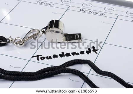 A silver whistle laying next to the word Tournament drawn on a calendar. - stock photo