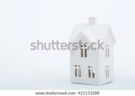 A simple, antique white porcelain house sitting on a white background. A delightful photo for a variety of ideas and concepts with plenty of room for text. horizontal, copy space. - stock photo