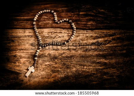 A simple beaded olive wood cross or rosary rests upon a rustic table laid out in the shape of a heart. Symbols of Christ & love.  Filtered for a vintage retro faded look.  - stock photo
