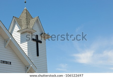 A simple black cross marks the faith of a white country church with a blue sky and wispy clouds.
