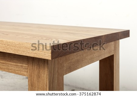 A simple(minimal) oak wood office desk(dining table) on the vintage white bottom, white wall. - stock photo