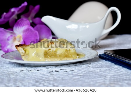 A simple slice of delicious fresh baked apple pie with a crunchy cover of puff pastry and a delicious filling of apples and cinnamon served with vanilla sauce - stock photo