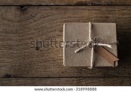 A simple, string tied gift box or package with a blank vintage style label tag.  Shot overhead on an old oak wood planked table. - stock photo