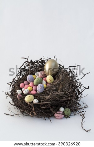 A simple, vintage bird's nest filled with Easter egg candy with a prize of a golden egg sitting on top. A plain white vertical background with copy space room. - stock photo