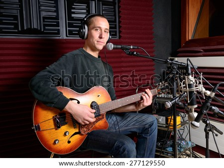 a singer and his guitar in a recording studio - stock photo