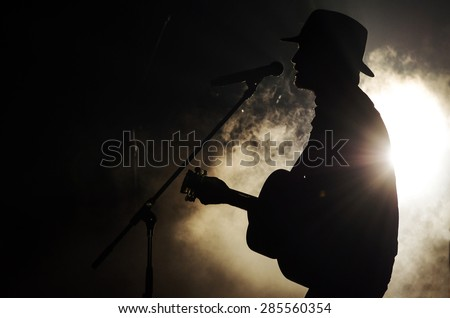 A singer man silhouette playing guitar - stock photo