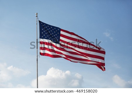 A single American flag flying high as the wind helps it to spread its colors in the late afternoon sun. Fluffy clouds and a blue sky make the perfect background. Horizontal format with copy space.