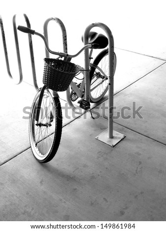 A single bike with basket in a bike rack in a city - stock photo