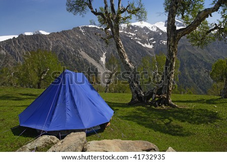 A single blue tent in the Himalayas, with the mountains in the background. - stock photo
