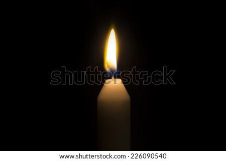 A single burning white candle isolated on black background - stock photo